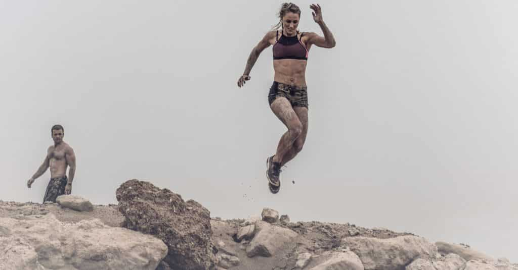bounce back from failure strong woman leaping through mud