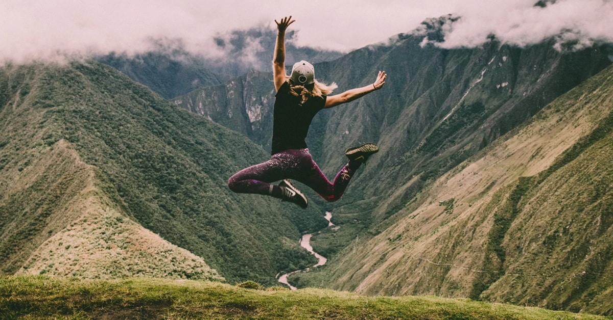 grateful woman jumping on top of mountain