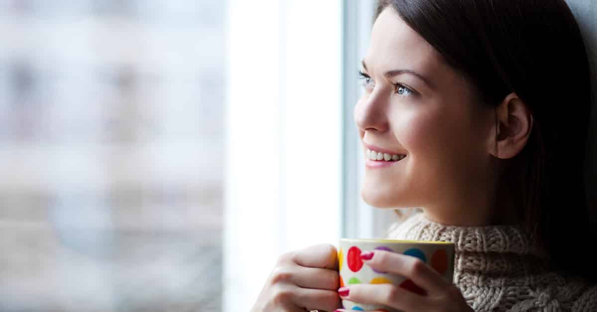 woman reflecting on new years goals with coffee by a window