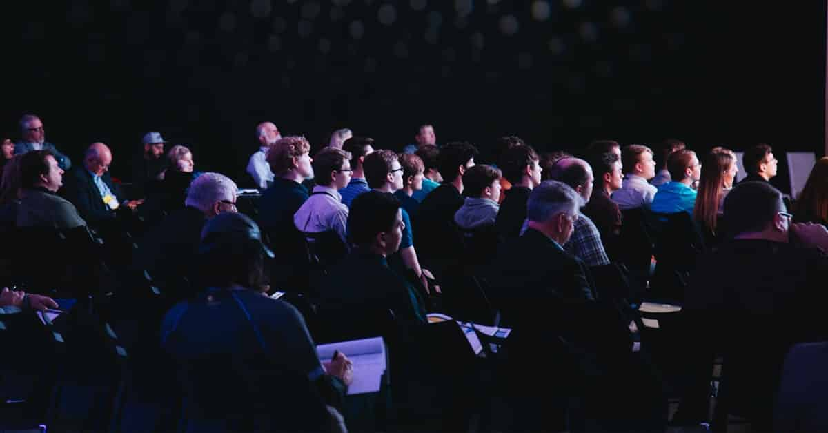 people sitting in dark audience at conference