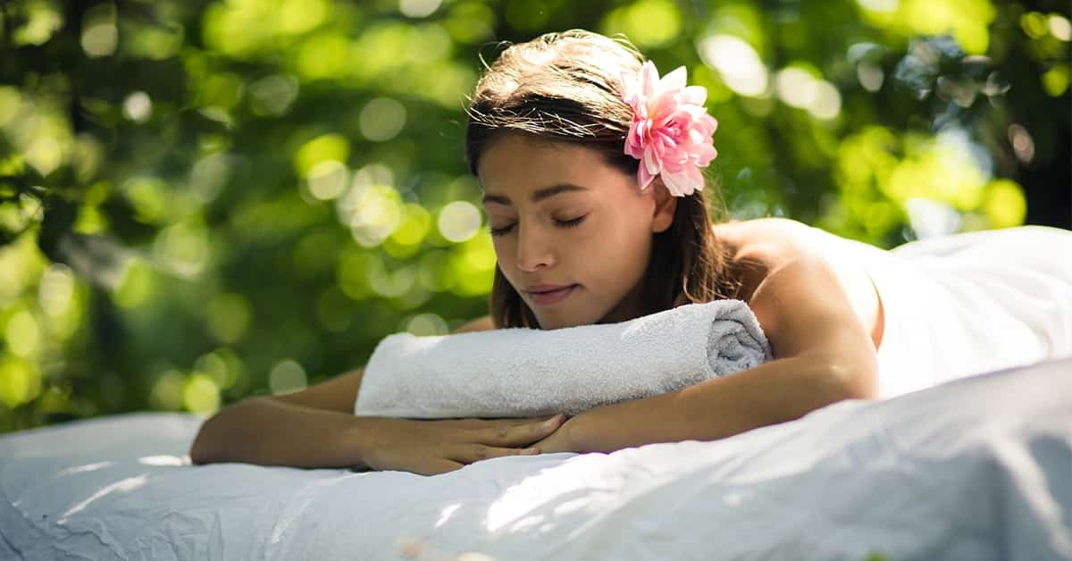 beautiful woman laying face down on a matress in the woods