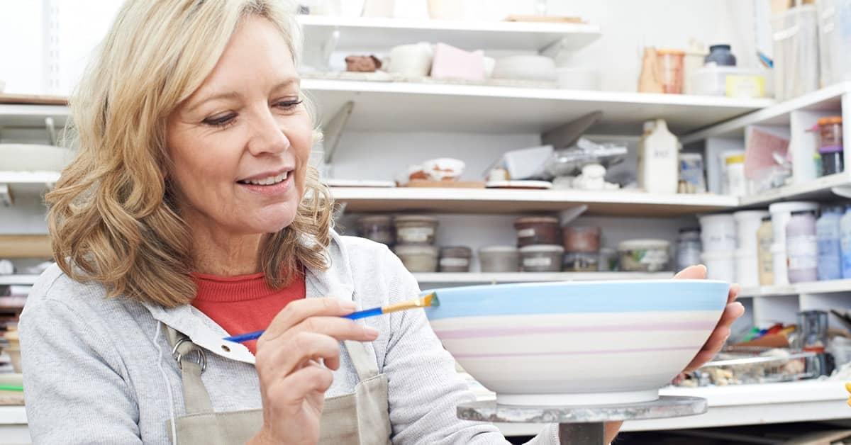 older woman painting ceramic