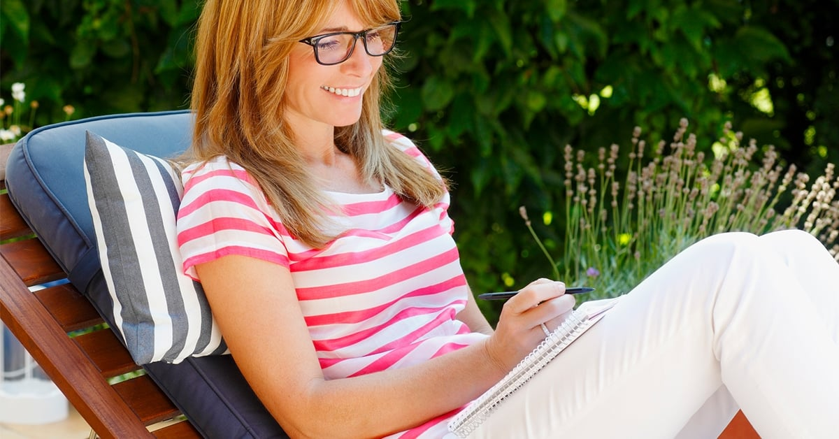 red head woman sitting on lounge chair with journal