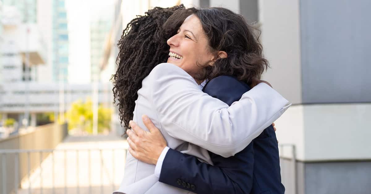 two women hugging outside a matress store