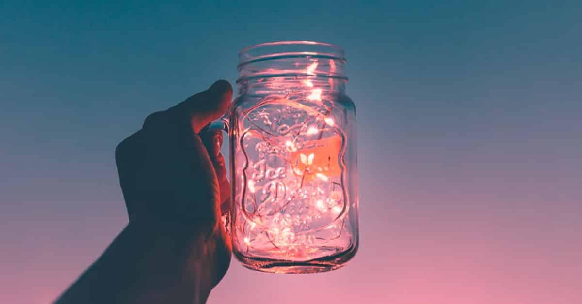 mason jar of fairy lights held against night sky