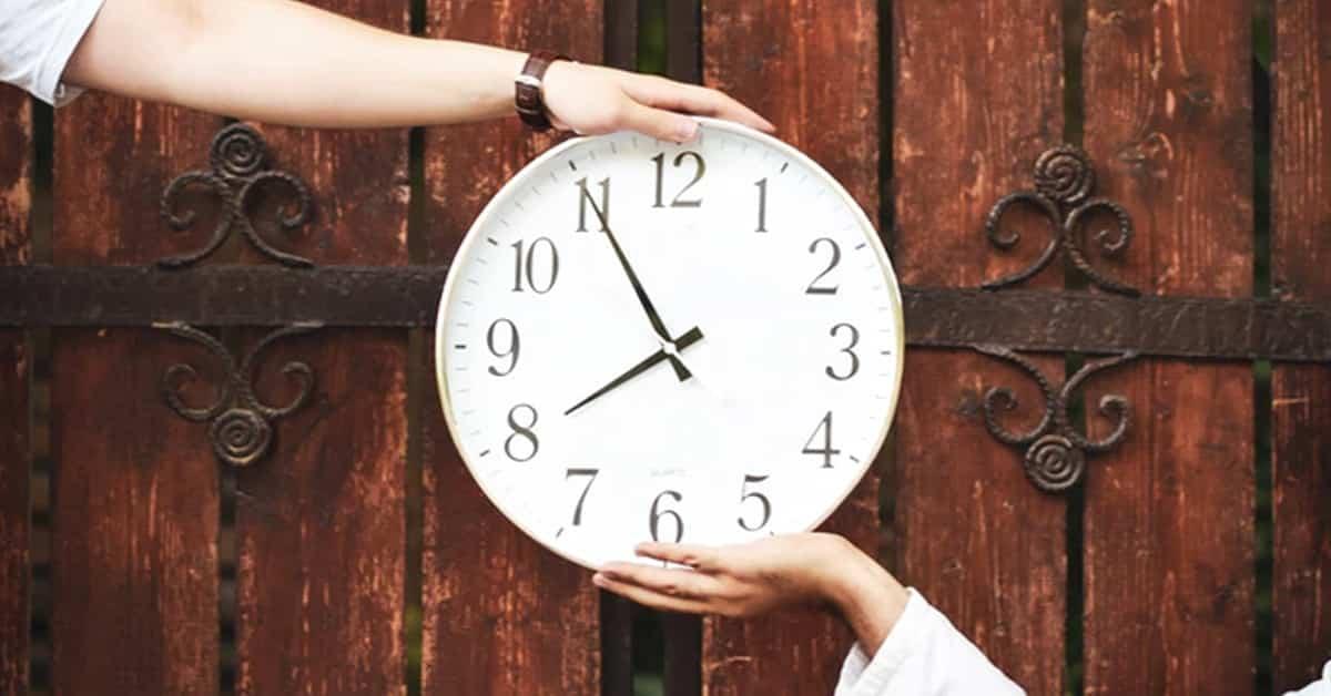 two hands holding clock wooden door