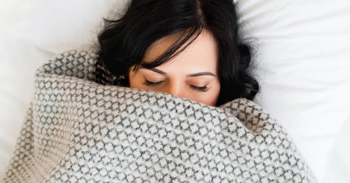 woman under the covers with eyes shut and blanket snuggled around mouth