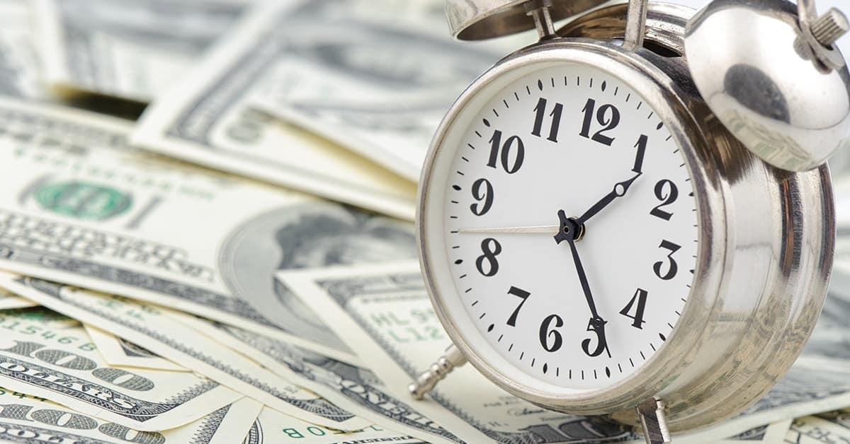 alarm clock on stack of dollar bills