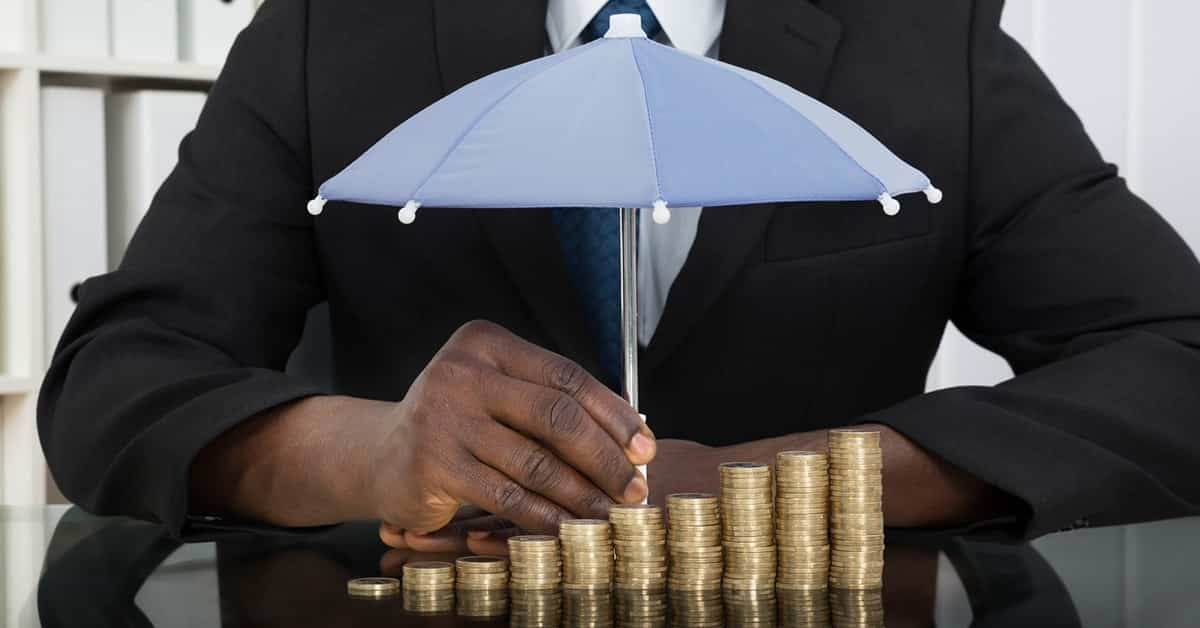 banker holding tiny umbrella over stacks of gold coins