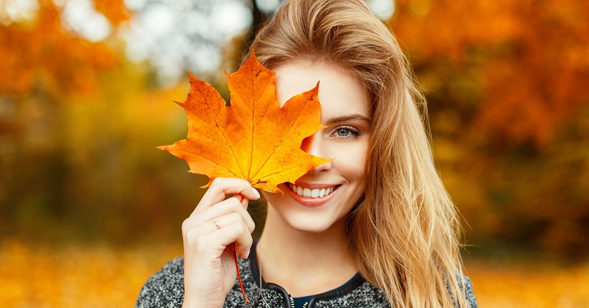 smiling woman holding large maple lead over eye in autumn