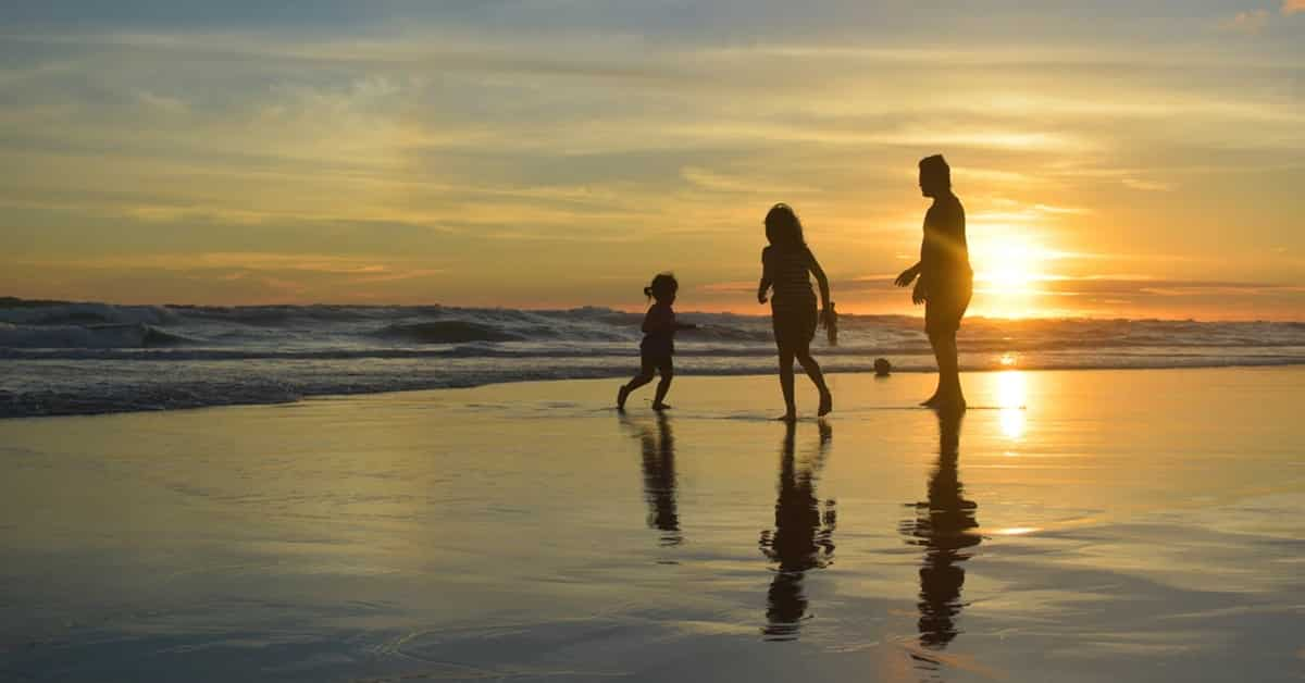 family playing on beach at dusk