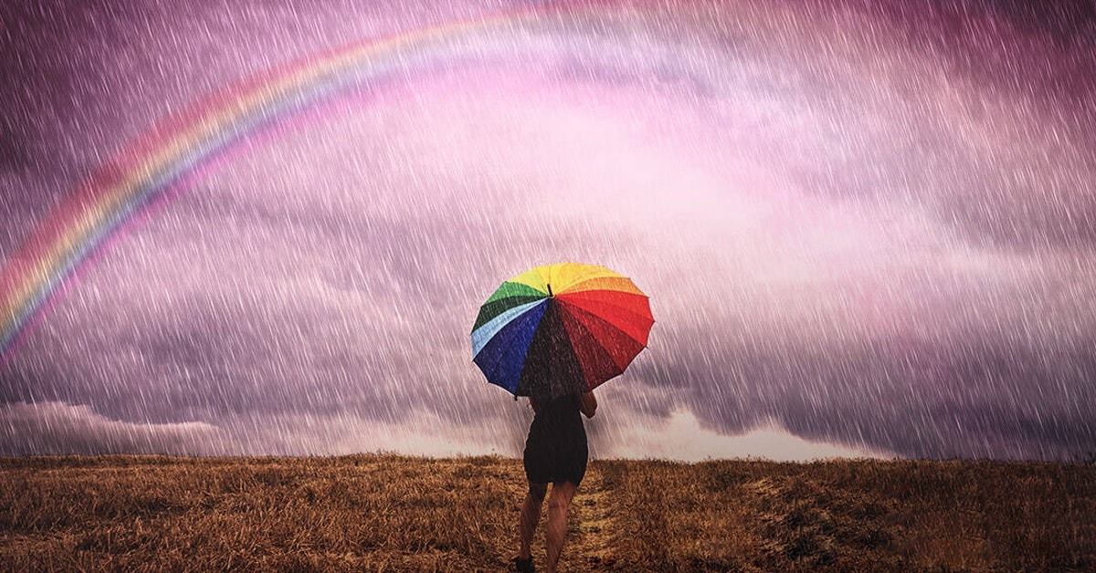 abstract figure holding umbrella watching rainbow in sky