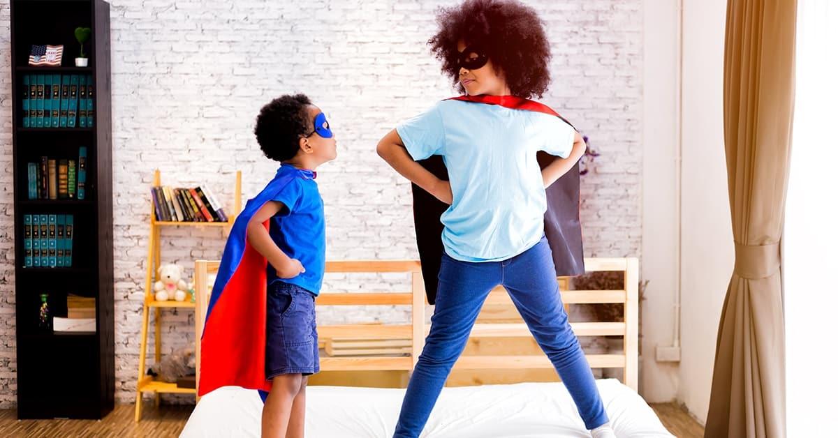 super hero kids standing on beds in costume