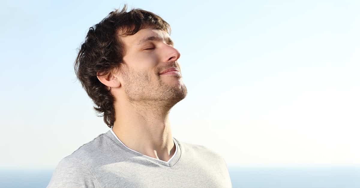 man looking refreshed and breathing deeply
